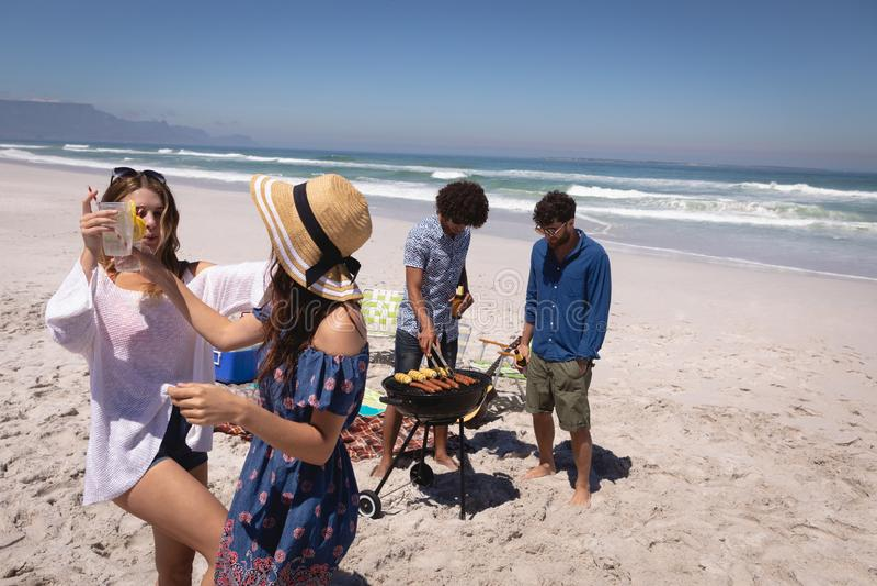 Vue de face de deux amis de femmes dansant tandis qu'amis d'hommes faisant un barbecue images stock