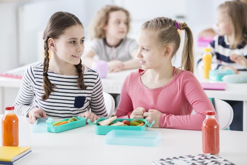 Vue de face de deux filles s'asseyant par un bureau d'école avec le lun ouvert image stock