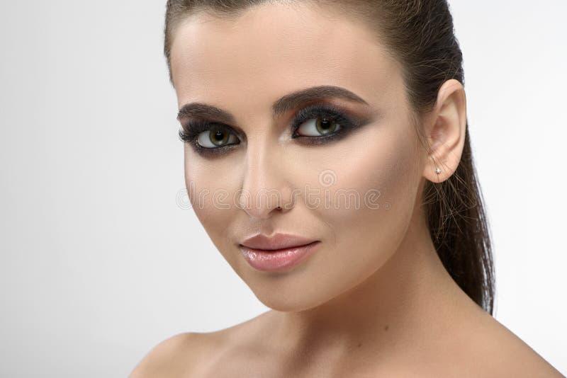 Vue de face du maquillage de port de soirée de fille posant avec les cheveux recueillis photo libre de droits