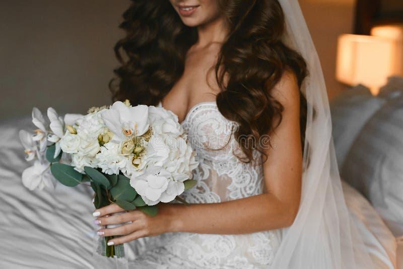Vue de face de femme dans la robe de mariage gardant le beau bouquet image libre de droits