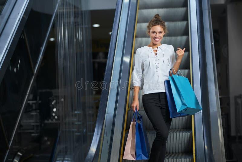 Vue de face de femme heureuse avec apprécier de nouveaux achats dans le mail photos stock