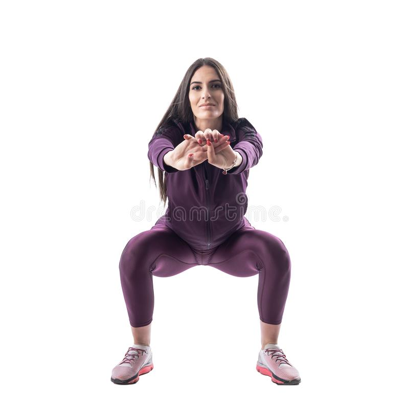 Vue de face de l'entraîneur attirant aérobie ou de forme physique faisant des exercices accroupis photo libre de droits