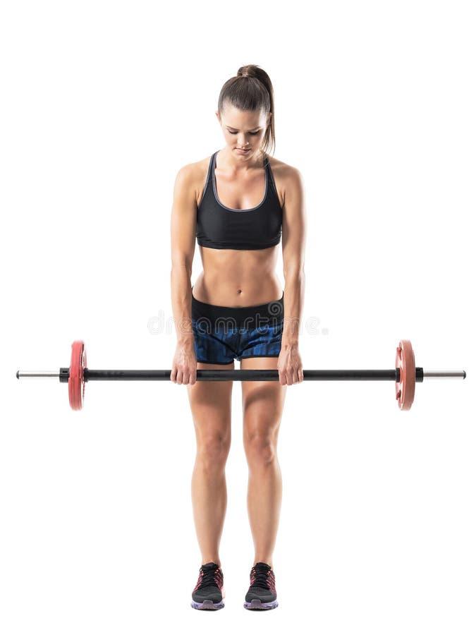 Vue de face de la femme sportive musculaire forte faisant l'exercice mort d'ascenseur avec le barbell photos libres de droits