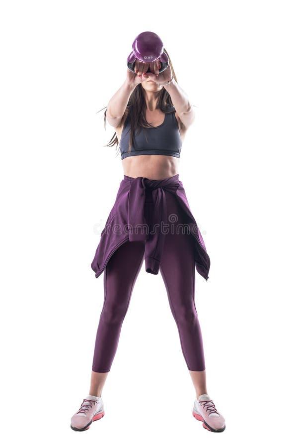 Vue de face de la jeune femme méconnaissable de forme physique s'exerçant et balançant avec le kettlebell photo libre de droits