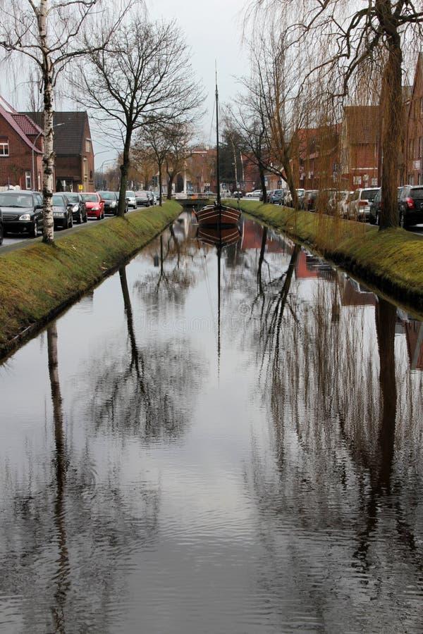 Vue de face large sur un bateau de marin et sa réflexion au canal et l'entourage dans le papenburg Allemagne photo stock