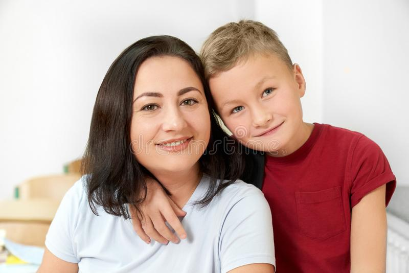 Vue de face de mère heureuse posant avec peu de fils photo stock