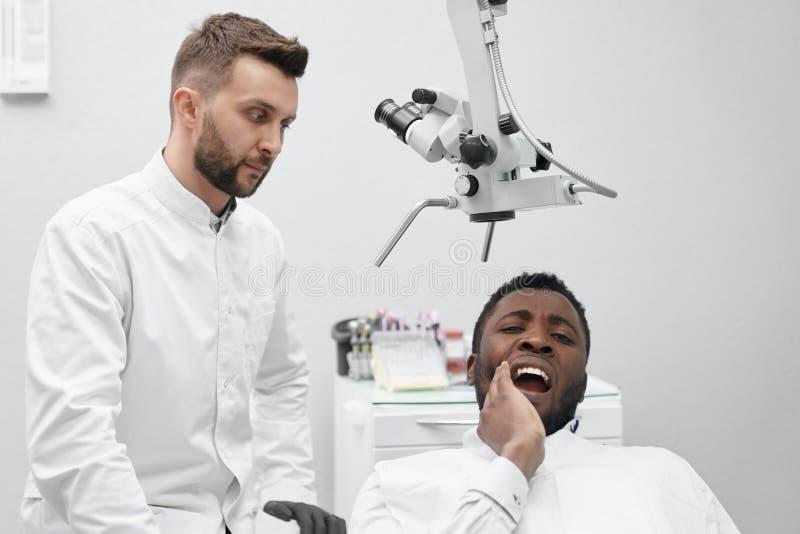 Vue de face de patient masculin africain avec la dent douloureuse image libre de droits