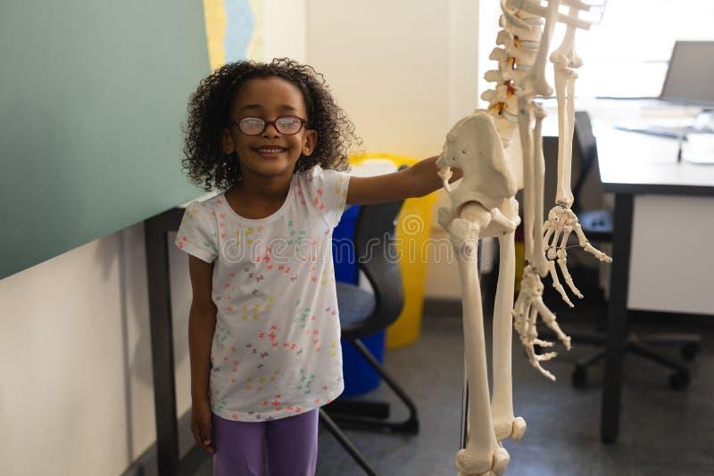 Vue de face de peu d'écolière noire heureuse tenant le modèle squelettique humain et regardant la caméra en Cl photo libre de droits