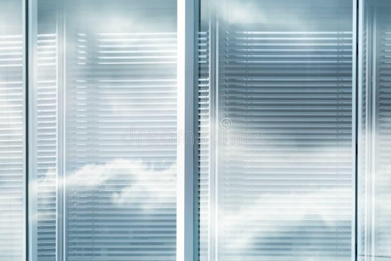 Vue de fenêtre d'auvents de l'immeuble de bureaux moderne avec la réflexion du ciel avec des nuages, effet brouillé images stock