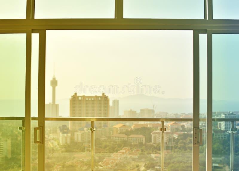 Vue de fenêtre et de haut bâtiment au coucher du soleil photos stock