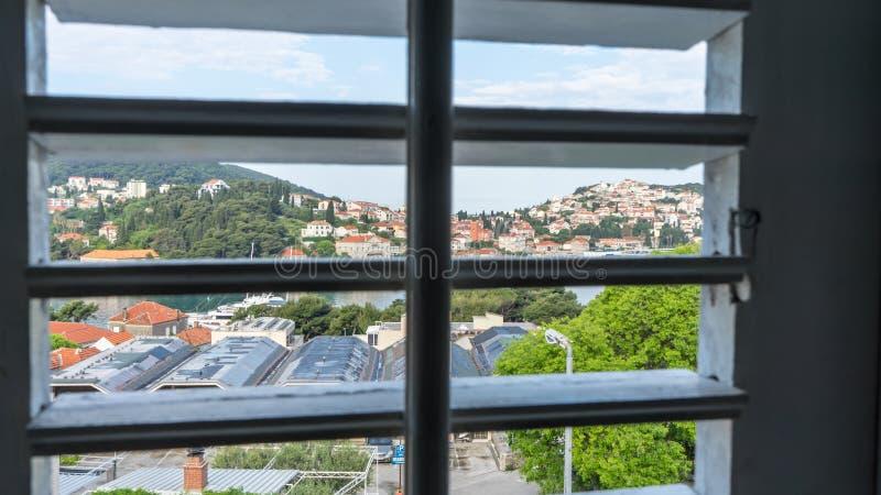 Vue de fenêtre par les abat-jour Ville de l'intérieur de la maison Ville de mer dans une vue de colline des volets en bois images stock