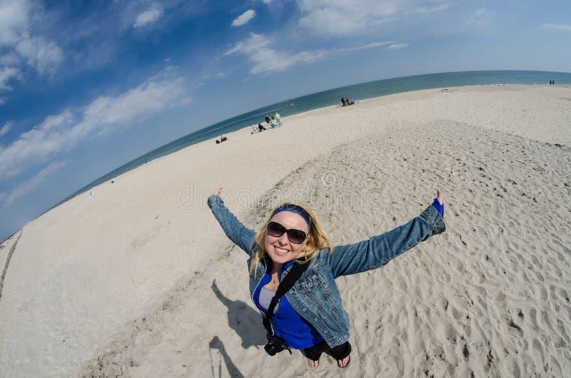 Vue de fisheye d'amusement de femme blonde appréciant la plage à l'île d'Assateague image stock