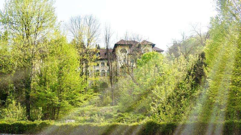 Vue de grand hôtel abandonné avec la vieille architecture hiddent dans la forêt dans une journée de printemps ensoleillée photographie stock