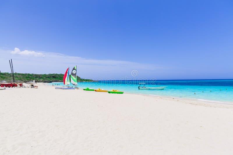 vue de invitation de plage tropicale de sable blanc avec des personnes détendant à l'arrière-plan le jour ensoleillé images libres de droits