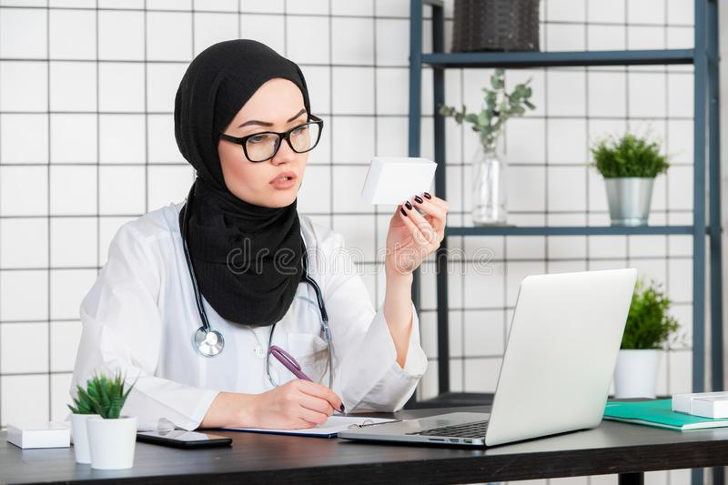 Vue de jeune docteur musulman avec la boîte de médecines de pilules images stock