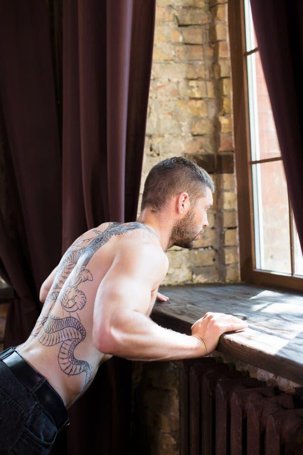 Vue de jeune homme faisant des pousées de rebord de fenêtre image libre de droits