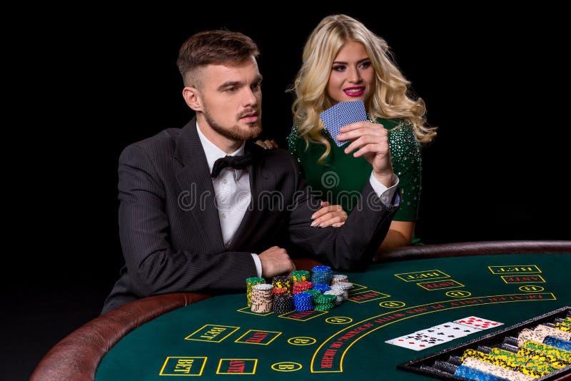 Vue de jeune, sûre, homme avec la dame tandis qu'il ` s jouant le jeu de poker photos stock