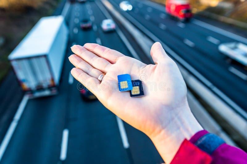 Vue de jour de main de femme tenant des cartes de sim au-dessus d'autoroute BRITANNIQUE image libre de droits