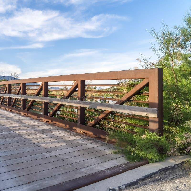 Vue de jour ensoleillé de place d'un pont avec la rambarde en bois de plate-forme et en métal au-dessus d'un lac photographie stock