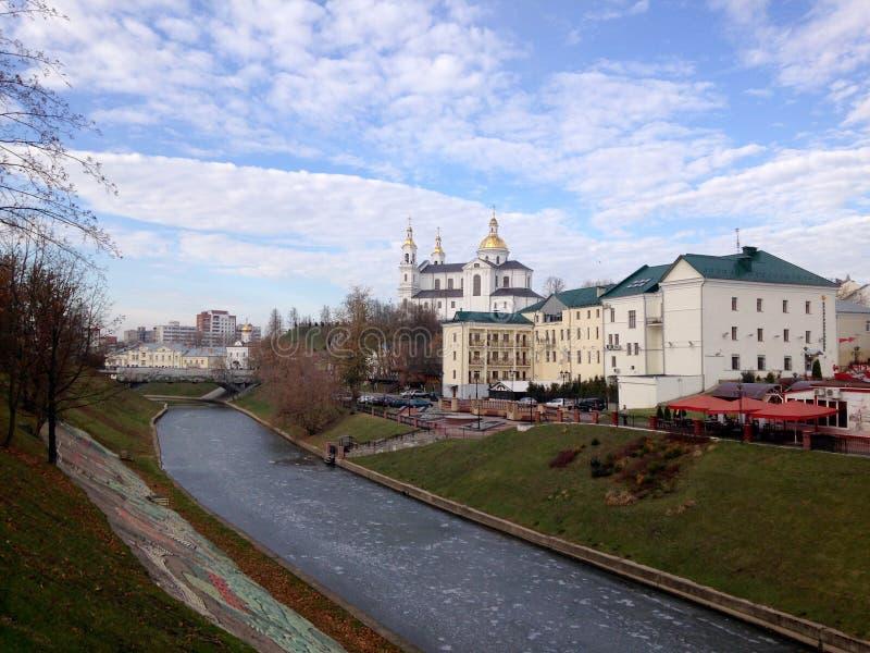 Vue de l'église et des bâtiments derrière la rivière, couverte de la glace, contre le ciel bleu avec des nuages Vitebsk, Belarus photographie stock libre de droits