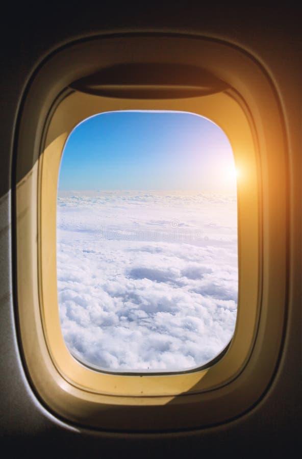 Vue de l'avion de fenêtre sur le ciel étonnant avec les nuages scéniques au coucher du soleil photo stock