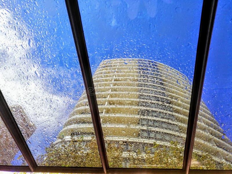 Vue de l'immeuble ayant beaucoup d'?tages par des gouttes de pluie sur la fen?tre claire photographie stock libre de droits