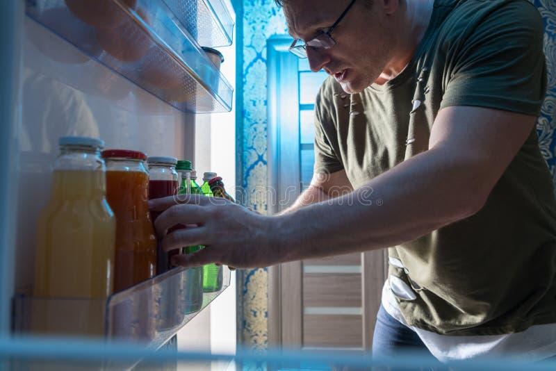 Vue de l'intérieur d'un réfrigérateur d'un homme prenant un jus photographie stock libre de droits