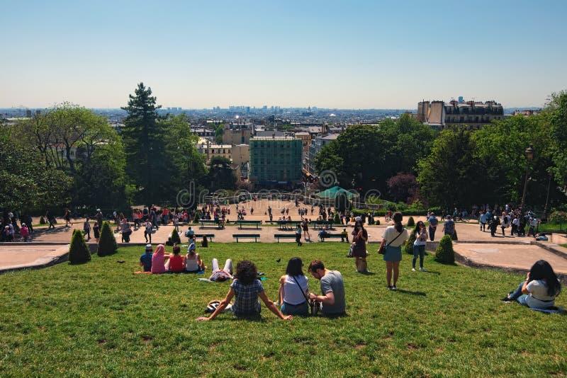 Vue de la colline de Montmartre à la pelouse verte devant l'église de Sacre Coeur avec des touristes détendant et appréciant photos stock