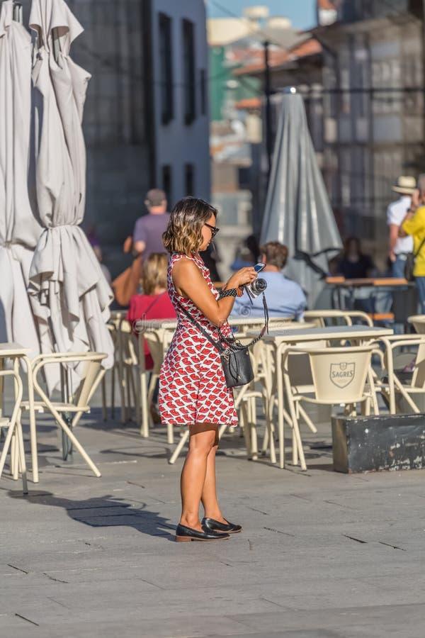Vue de la femme à l'aide du téléphone portable dans la rue, avec la valise et la caméra à disposition, style de pin-up, terrasse  photographie stock libre de droits