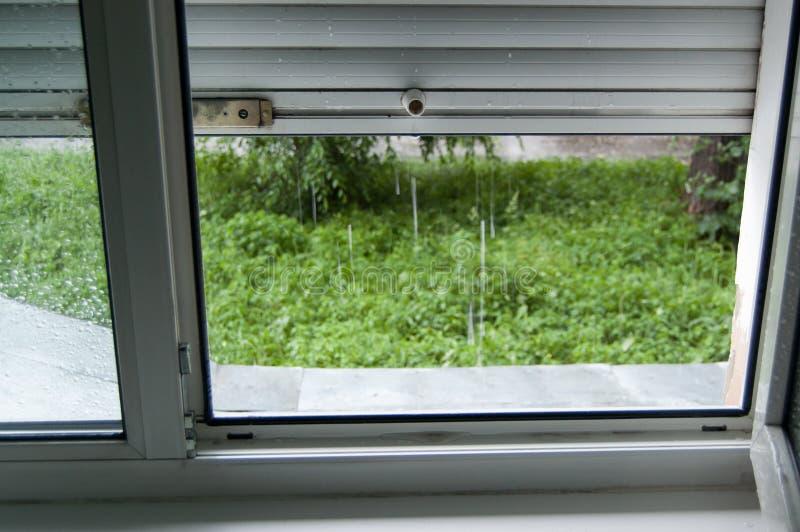 Vue de la fenêtre avec des volets à l'extérieur où il pleut images stock