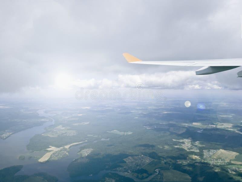 Vue de la fenêtre des avions sur les champs et les forêts sans fin, des nuages et de l'aile des avions avec un reflet de lumière image libre de droits