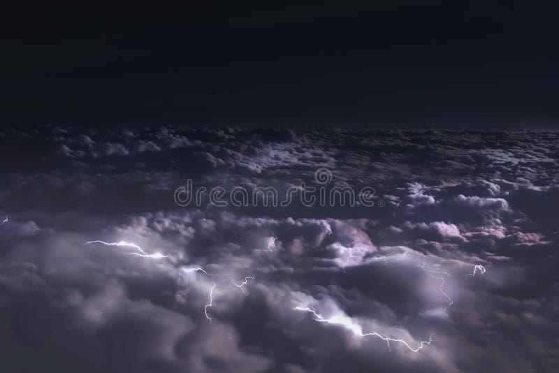 Vue de la fenêtre de l'avion aux nuages à la nuit et aux éclairs images stock