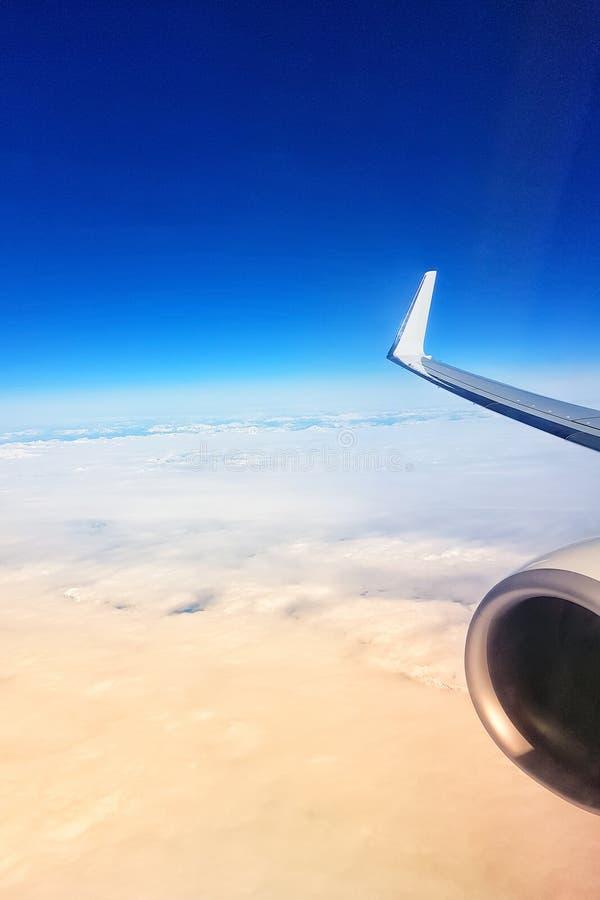 Vue de la fenêtre plate aux nuages et au ciel pendant le vol au coucher du soleil image libre de droits