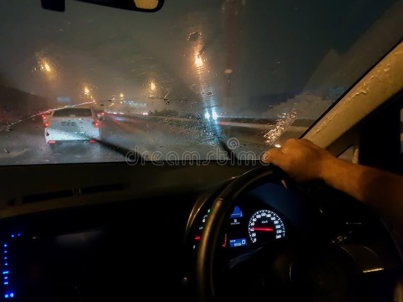 Vue de la fenêtre de voiture à la route couverte par des gouttes de pluie tout en conduisant la voiture photographie stock libre de droits