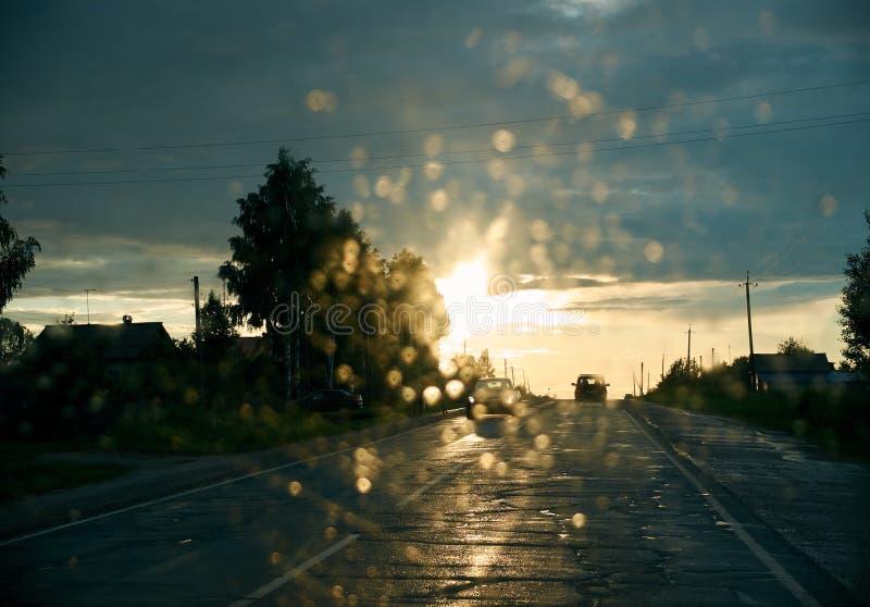 Vue de la fenêtre de voiture sur la route en avant pendant le beau coucher du soleil photographie stock libre de droits