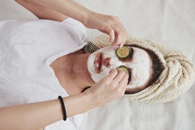 Vue de la fille en haut d'un masque de beauté blanc sur le visage et anneaux de concombre sur les yeux images libres de droits