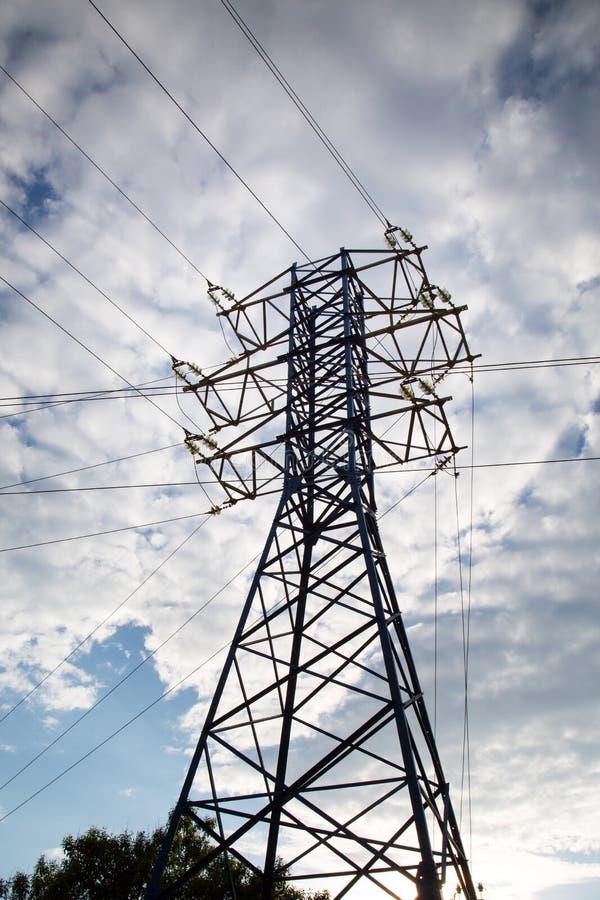 Vue de la ligne électrique contre les nuages du ciel bleu à la lumière du soleil photos stock