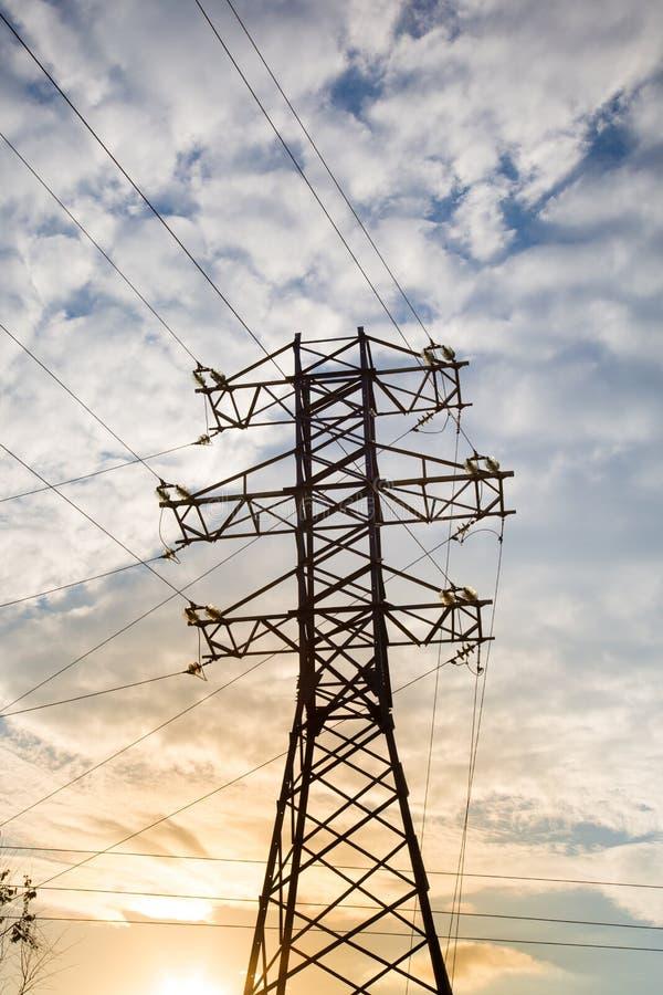 Vue de la ligne électrique contre les nuages du ciel bleu à la lumière du soleil image stock