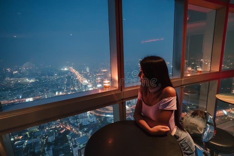 Vue de la m?tropole moderne la nuit Bangkok, Tha?lande La fille appr?cie un cocktail d?licieux ? la barre sur le quatre-vingt-six photographie stock libre de droits