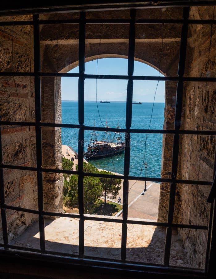 Vue de la mer et des bateaux par les barres sur la fenêtre dans la tour blanche à Salonique, Grèce images libres de droits