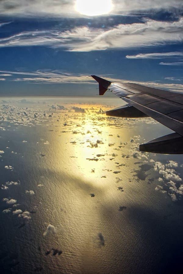Vue de la mer par la fenêtre d'un avion avec la réflexion du soleil dans l'eau et la fusée des gouttelettes d'eau sur le verre photos stock