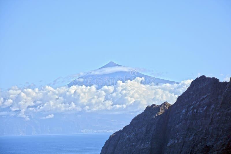 Vue de la montagne dans les nuages à travers la mer photos stock