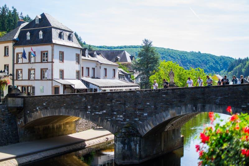 Vue de la notre rivière avec un pont en pierre dans la vieille ville de Vianden, Luxembourg, avec les maisons typiques au fond photos libres de droits