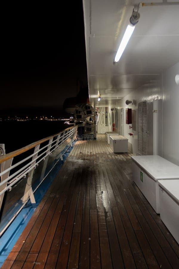 Vue de la nuit de la plate-forme d'un bateau avec la ville vue dans l'horizon photos stock