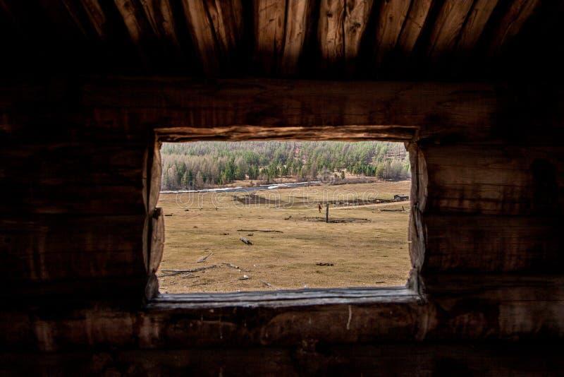 Vue de la petite fenêtre de rondin au champ avec une ferme et une rivière photos stock