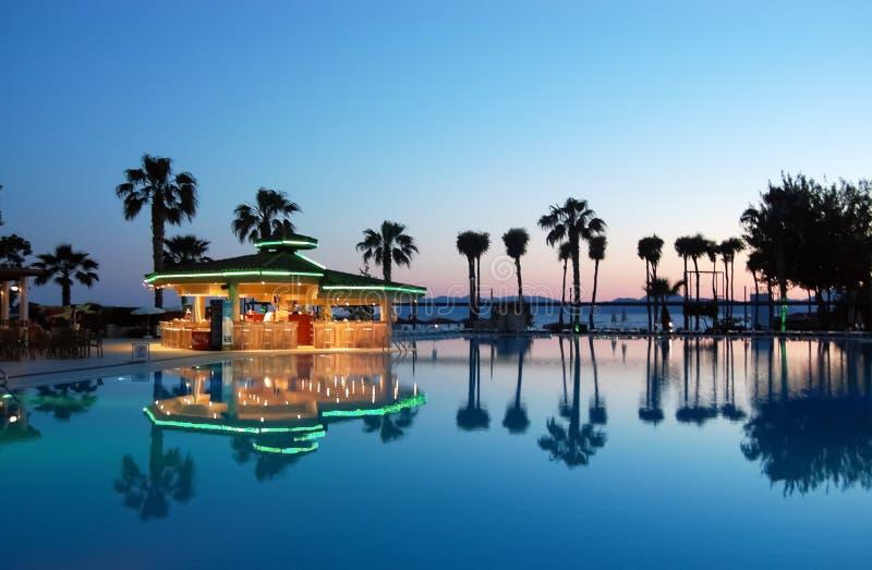 Vue de la piscine, de la barre de piscine et des palmiers au coucher du soleil dans h turc photographie stock libre de droits