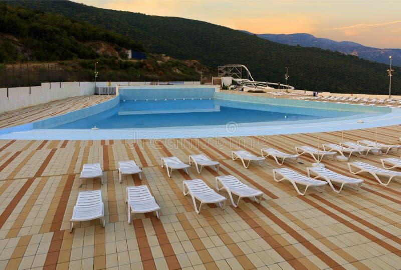 Vue de la piscine, des canapés du soleil et du parc aquatique vides de ville pendant le matin à l'aube photo libre de droits