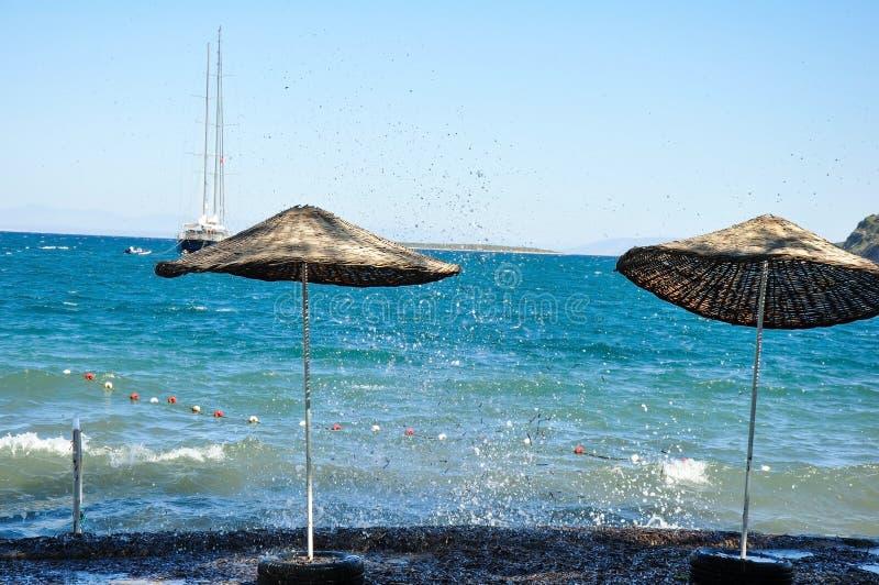 Vue de la plage avec deux parasols vers la mer Égée image libre de droits