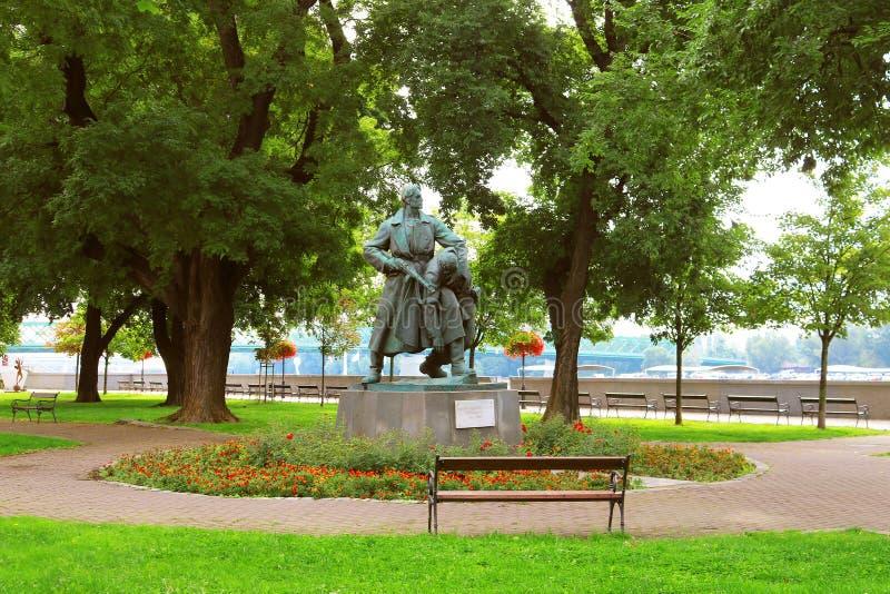Vue de la sculpture en bronze d'un partisan bulgare aidant son ami blessé par F David au quai de Vajanskeho, Bratislava photo stock