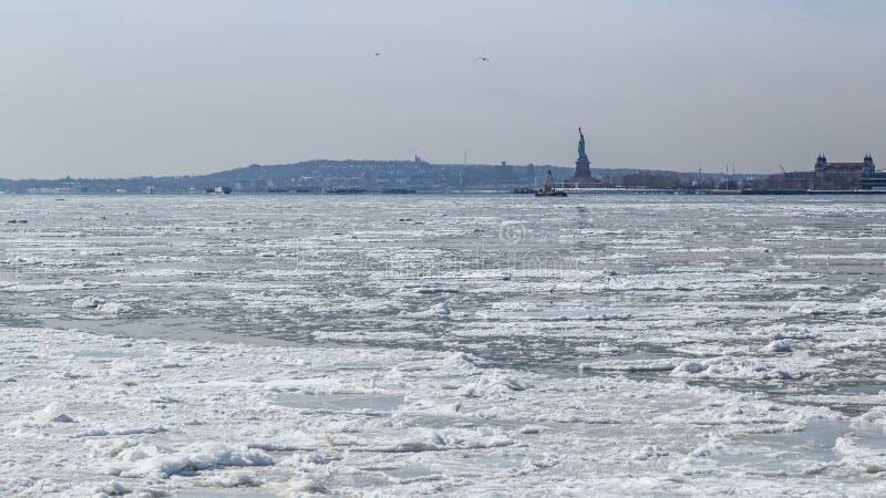 Vue de la statue de la liberté et de Jersey City à travers Hudson River congelé images libres de droits